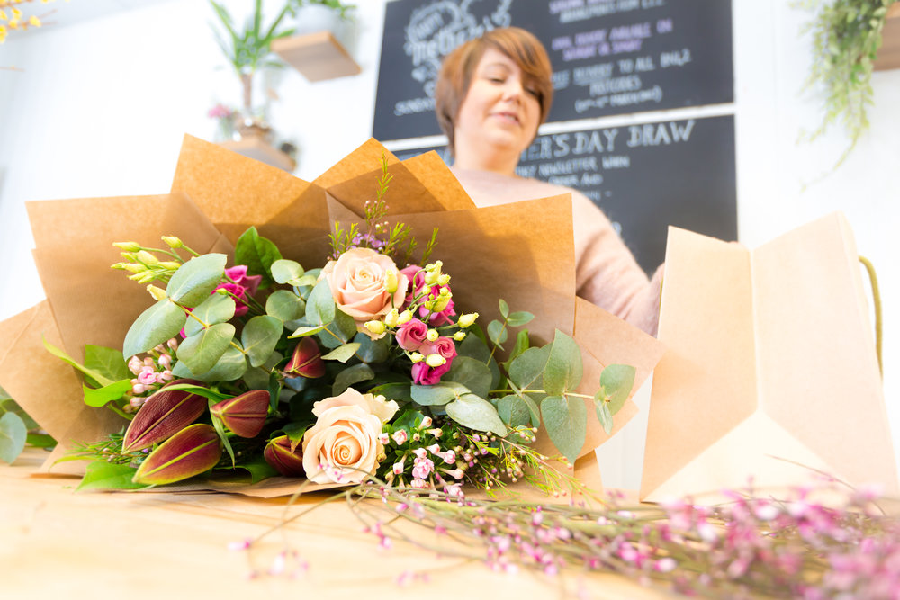 A florist make a bouquet for delivery in Brighton, using roses, lilies and eucalyptus.