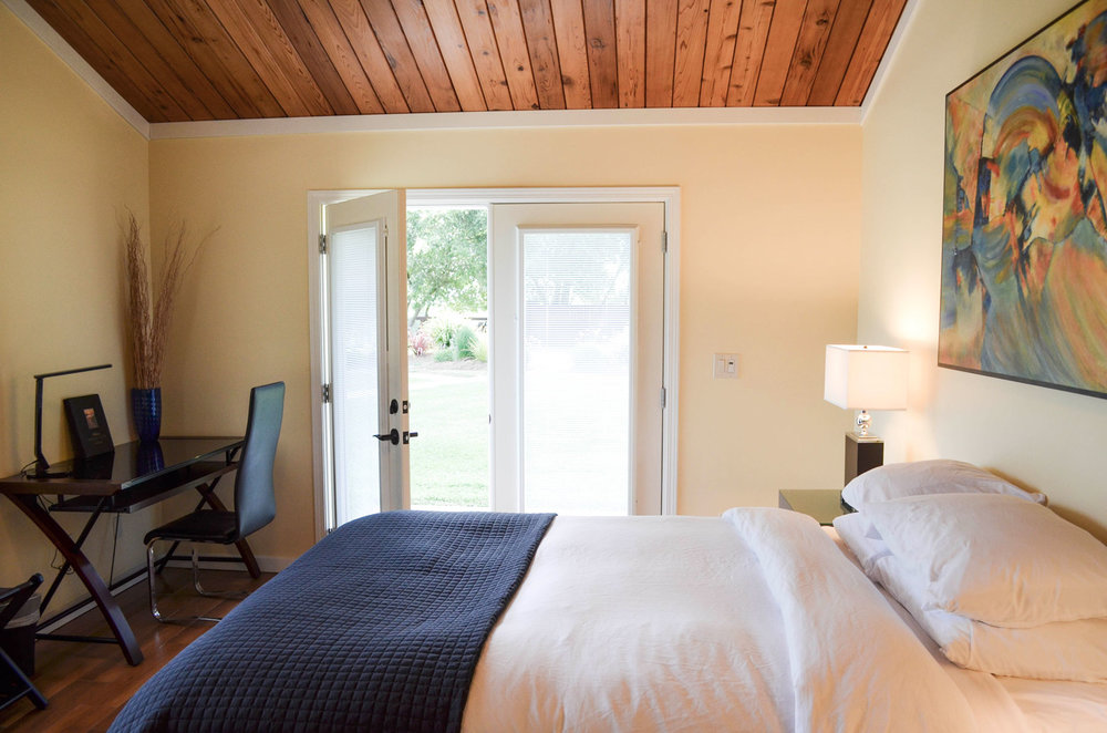 a well lit room with queen bed and desk at Indian Creek Inn just outside of Philo in Anderson Valley, California