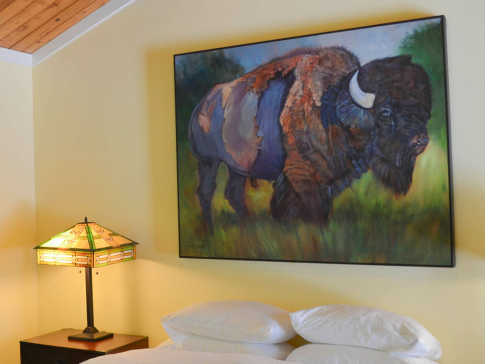 a painting of a buffalo sits above a bed in the Riverside building of Indian Creek Inn