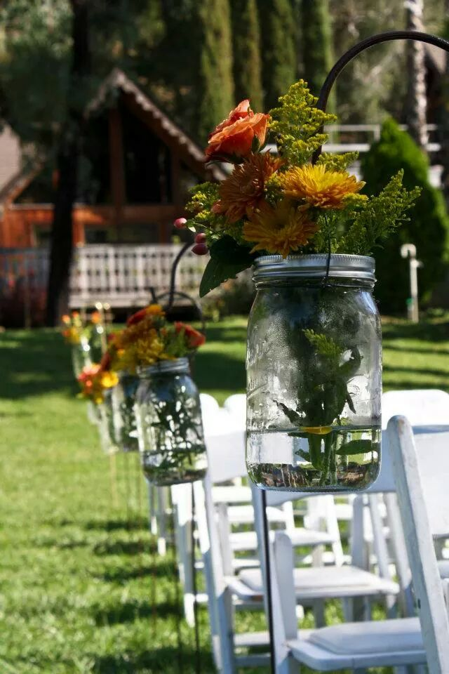 A mason jar with flowers brighten an outdoor wedding at Indian Creek Inn in Anderson Valley, CA