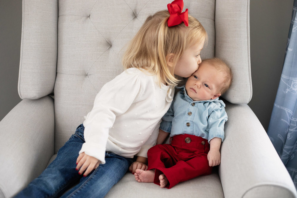 lifestyle newborn photography big sister kissing baby