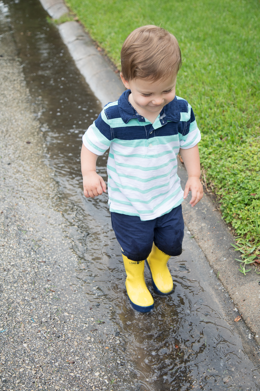 houston family lifestyle photography boy splashing in puddles with yellow rain boots
