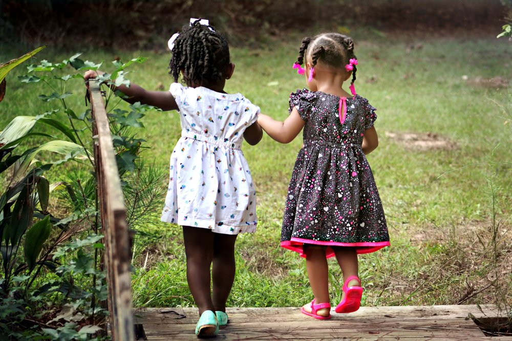 Children two girls holding hands outside