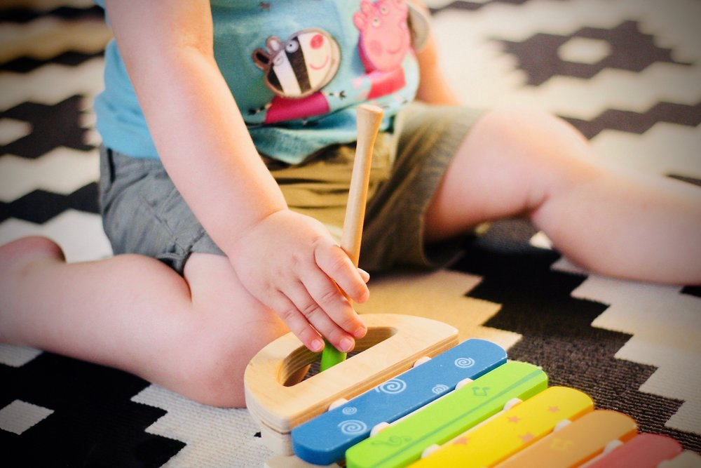 Child playing on floor with xylaphone