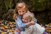 Two girls children hugging outside