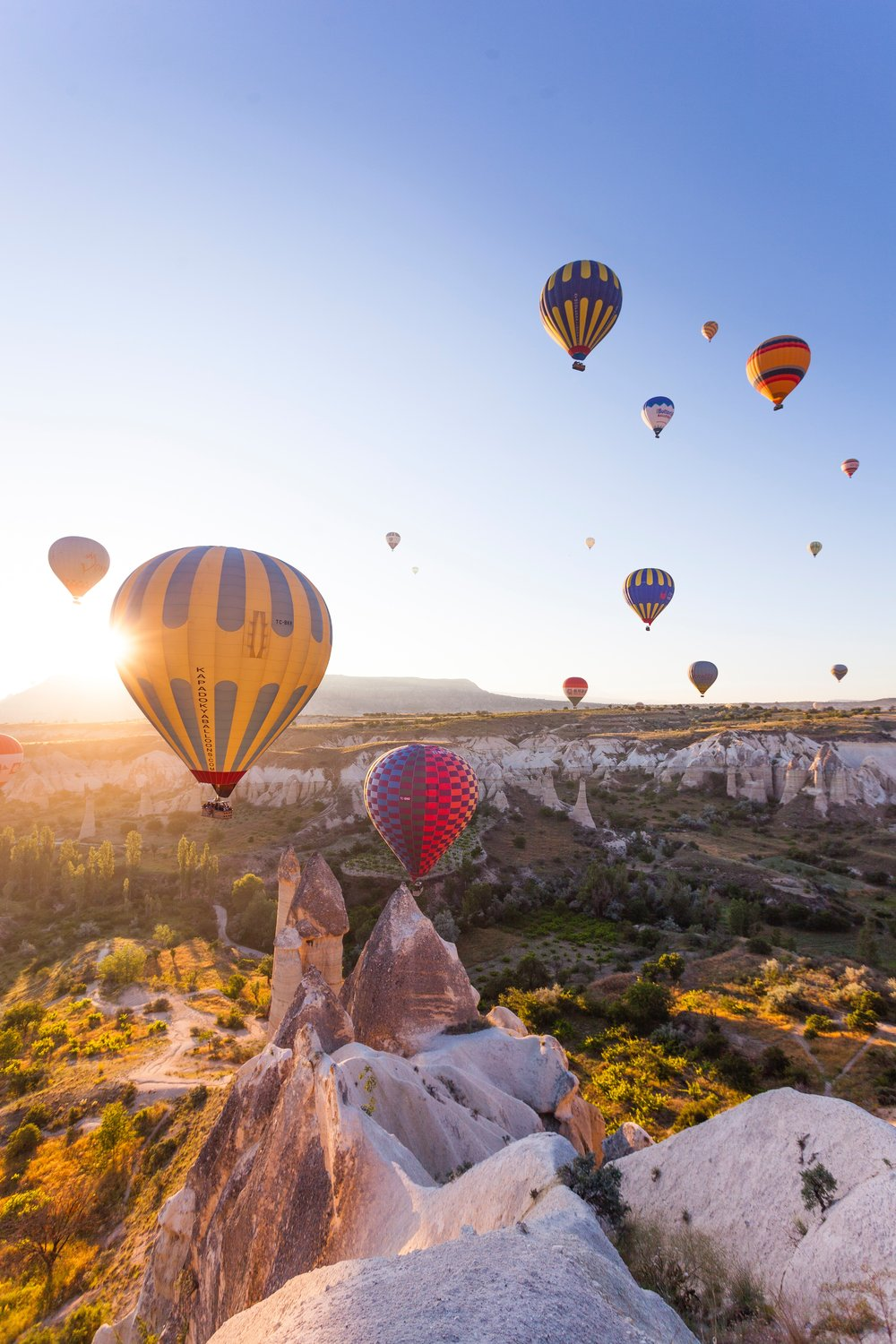 Spectacular view of colorful hot air balloons flying high in Cappadocia, Turkey. Cappadocia is a famous vacation destination for its panoramic desert views and cave homes.