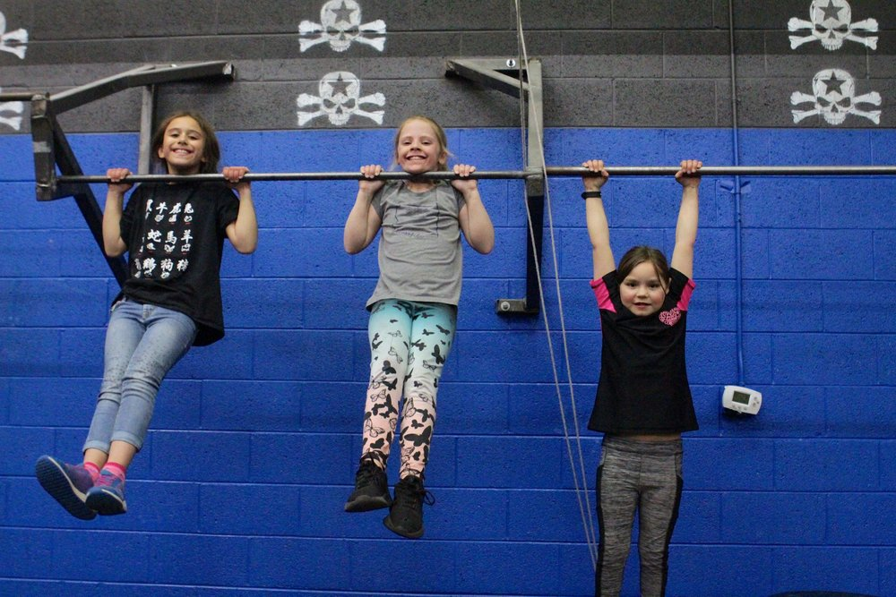 Look at these strong young ladies working on their pull-ups in kids class!