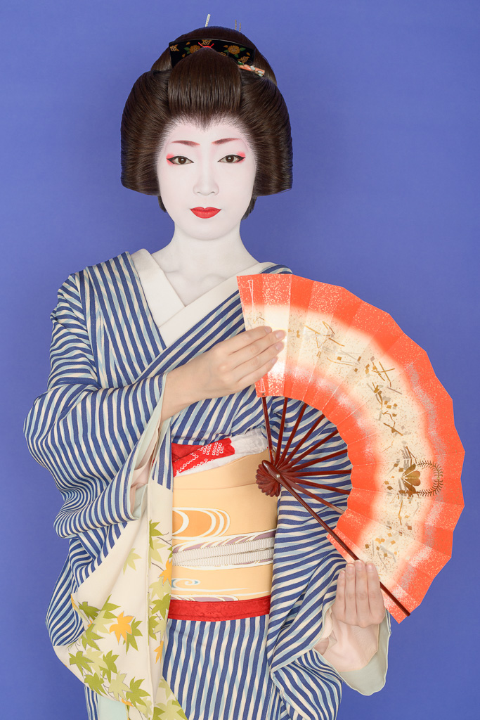 The geisha Toshikana of Miyagawa-cho in a blue and white striped kimono
