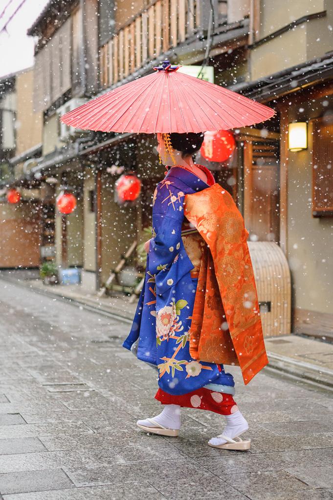 A maiko makes her way down Miyagawa-suji on a snowy day in March 2014
