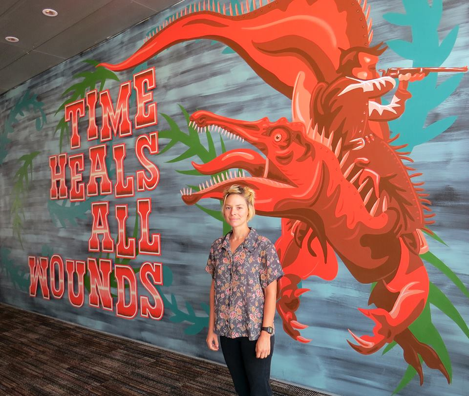 Artist Rachel Stiff with J.W. Caldwell's mural, Time Heals All Wounds, in the Primm Theater Lobby. (Photo JK Russ)