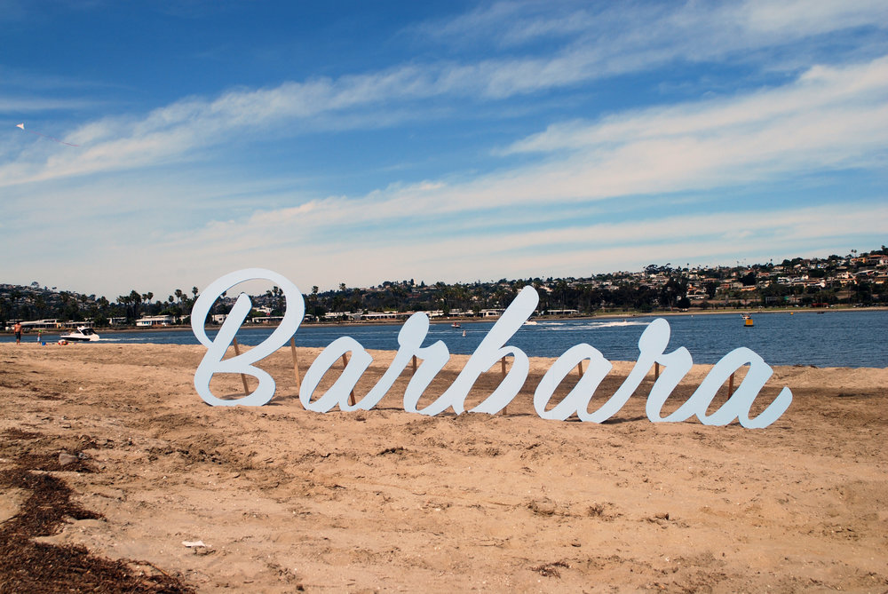 Sisters: Barbara , 2015, 5.5'h x 20'w, plywood and paint; Southern California ding-bat apartment signage dropped off at the beach for a day.