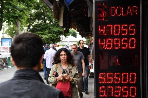 People pass a board displaying dollar and euro exchange rates in Turkish liras in Istanbul on May 23. (Ozan Kose/AFP/Getty Images)