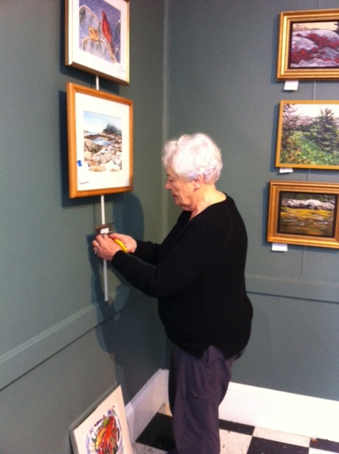 Claudette is busy hanging some of our smaller works.