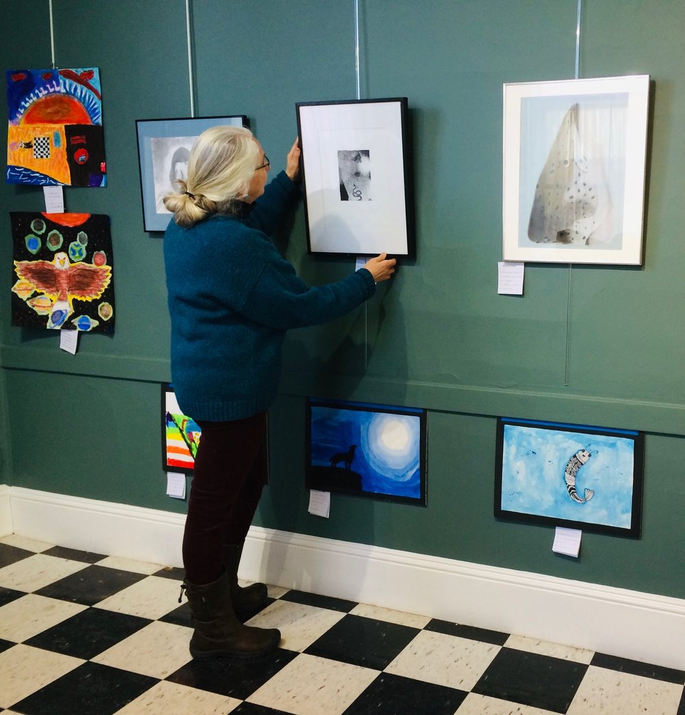 Laurie Burhoe at work hanging student art.
