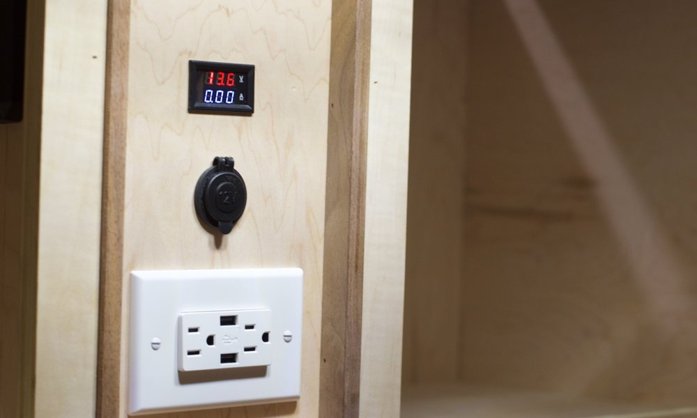 Voltage readout on top; 12v cigarette outlet and a 110v outlet with USB for mobile devices