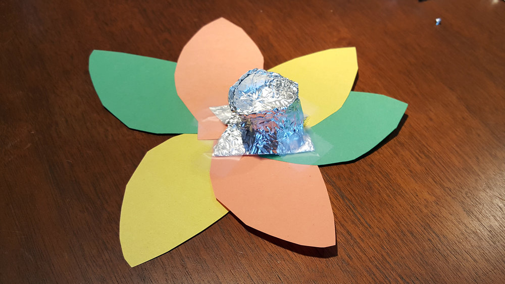The finished prototype. A small cap designed for a mouse's unique head shape with leaf-shaped, lightweight panels in colors that match the environment to obscure the wearer.
