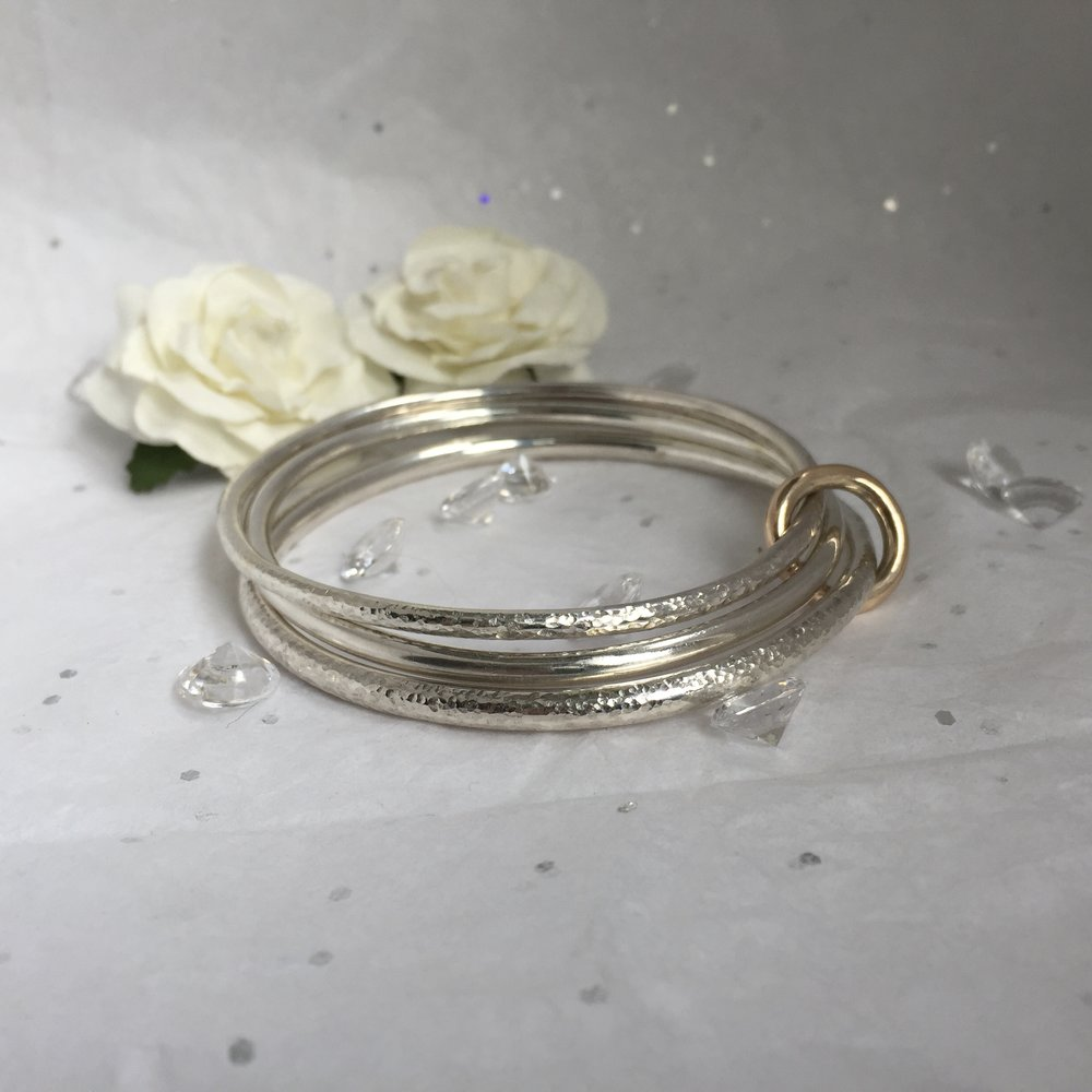 4234bd7d8a9 Set of Three Sterling Silver Bangles Held with a 9c Gold Ring — Jane Nevill