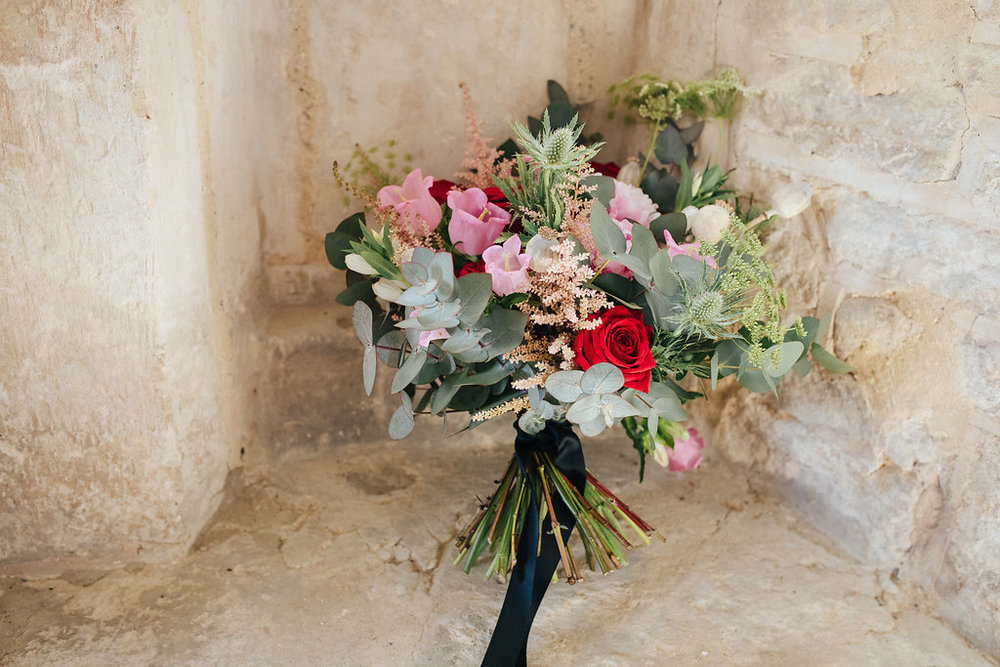 Hand-tied red rose and pink astilbe wedding bouquet