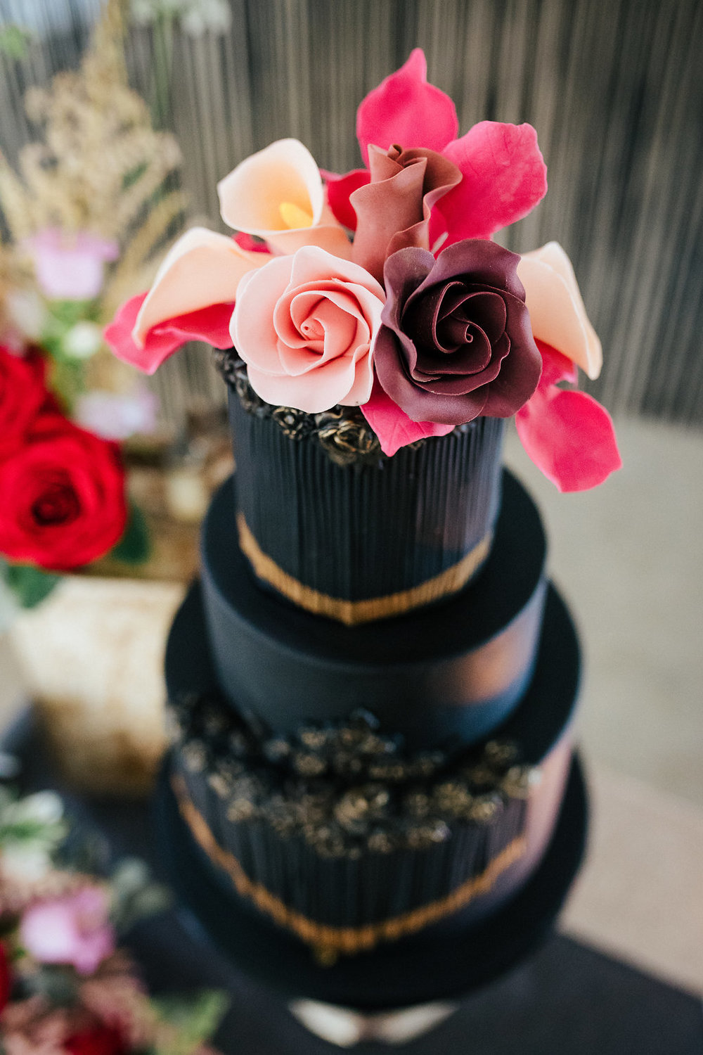 Black wedding cake with tassels and sugar flowers