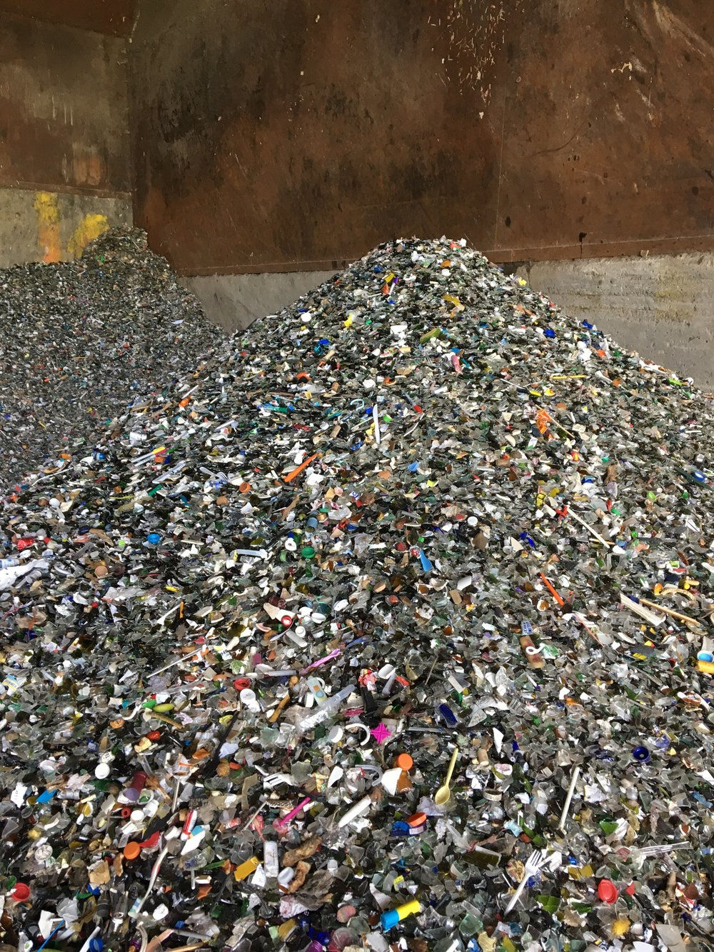 Glass line in a recycling facility (MRF). Most colored items in the picture are loose bottle caps.
