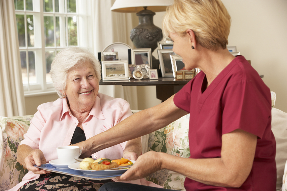 A caregiver serve food to an old aged woman