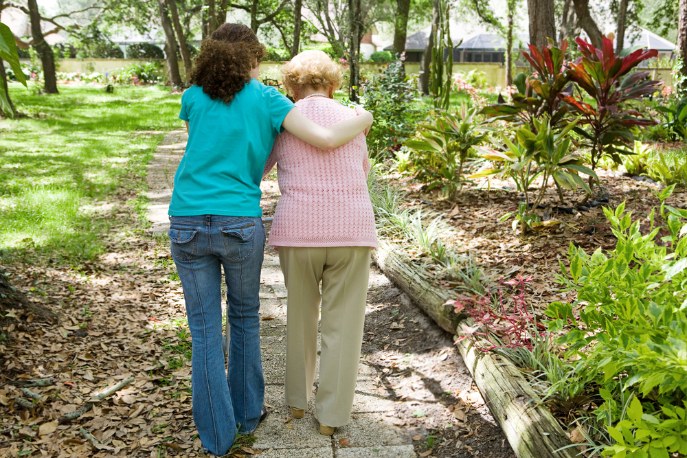 A woman help an old aged woman to walk