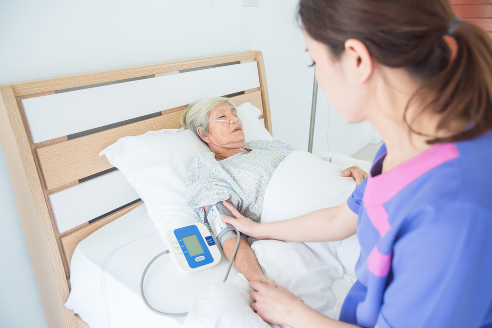 A caregiver  with a bedridden patient