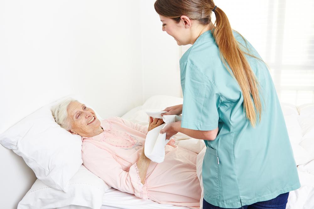 A caregiver helping a bedridden patient