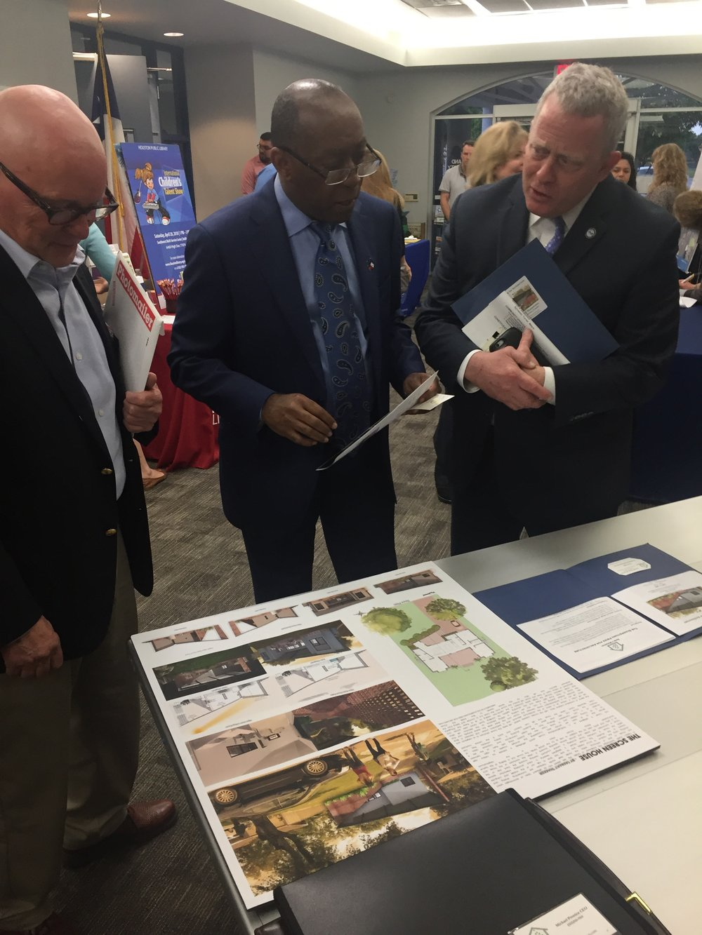 Michael Prentice showing display of winning design for the Sharpstown Prize for Architecture to Houston Mayor Sylvester Turner and Houston City Councilman David Robinson during the District J community meeting.