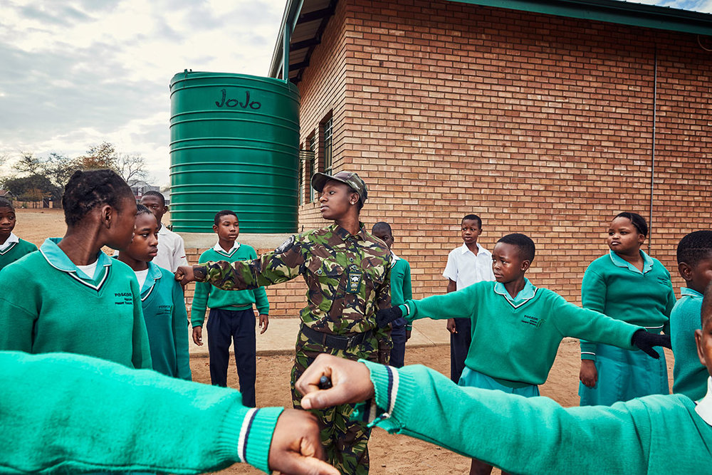 Black Mamba Nkateko Mzimba shows students how to properly stand at attention, Foskor Primary School, South Arica, 2017.
