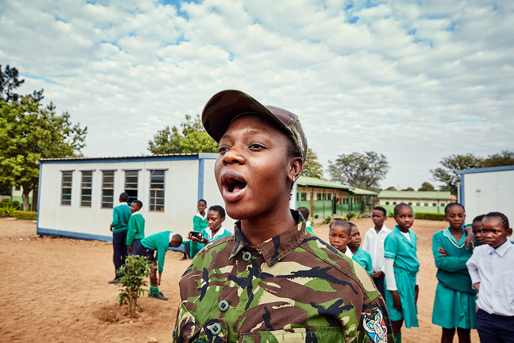 Black Mamba Nkateko Mzimba demonstrates how to shout orders to a group of school children, Foskor Primary School, South Arica, 2017.