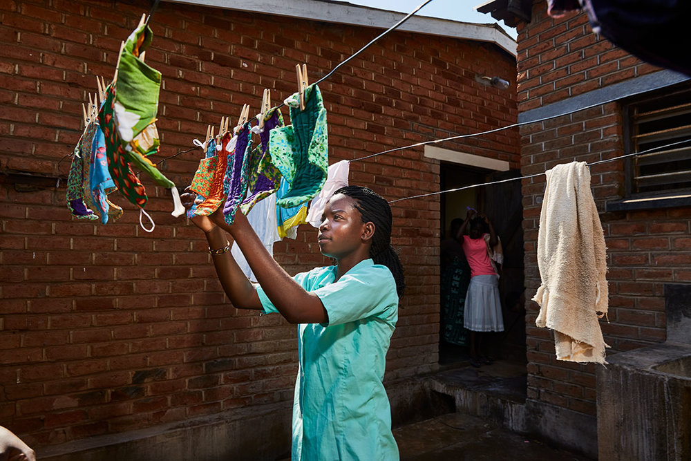 Tamanda hangs up the pads to dry after washing