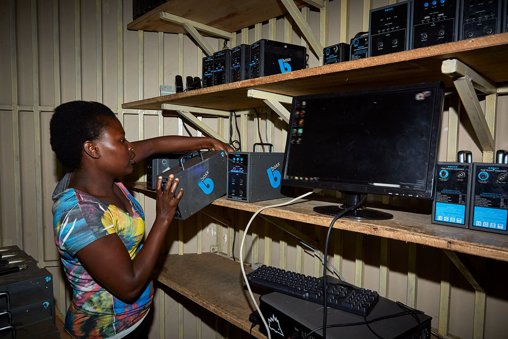 Jennifer, student at Green Malata, works at the electric kiosk, here solar batteries are rented out to the communities, Luchenza, southern Malawi, 2017.  Green Malata, an entrepreneurial training village that offers a variety of green alternatives to Malawi's notoriously unreliable national electricity provider, ESCOM, Luchenza, southern Malawi, 2017.