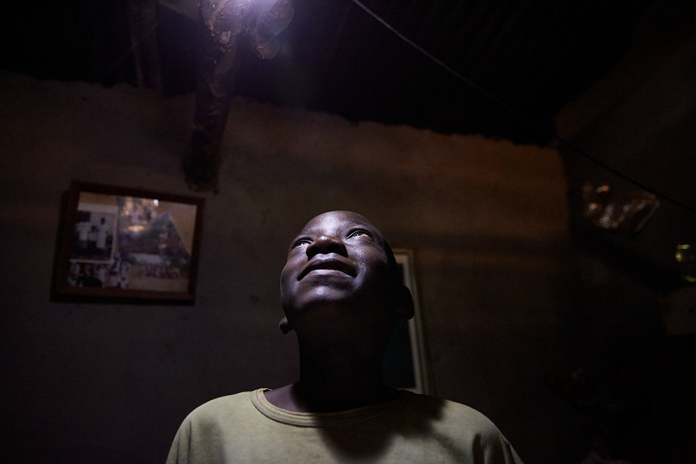 Jan Chumba (12) looks up at the solar battery run light at his home, Luchenza, southern Malawi, 2017.