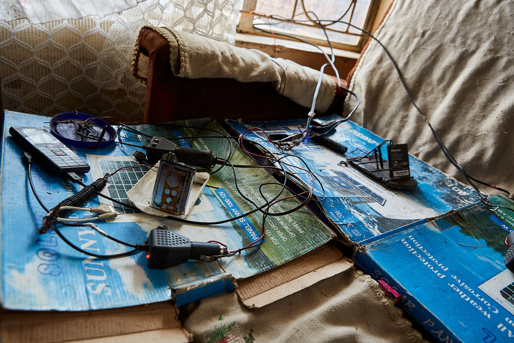"The charging station in the living room of Felix Wonga's home, Luchenza, southern Malawi, 2017.  The solar panels that Felix uses for his mobile phone charging business also powers their lights, and several small radio's and speakers. Felix: ""We are the only ones in this area that have a charging business. If more people in this area had solar panels it would very much improve their lives. ESCOM [the national provider], is too expensive and not reliable."""