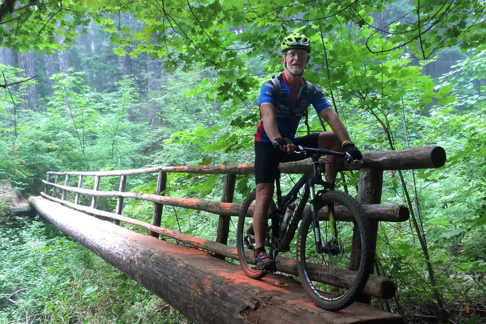 Bob Robinson, author of three bicycle guidebooks, crosses one of several single log bridges that crossed lower wetland areas on the McKenzie River Trail.