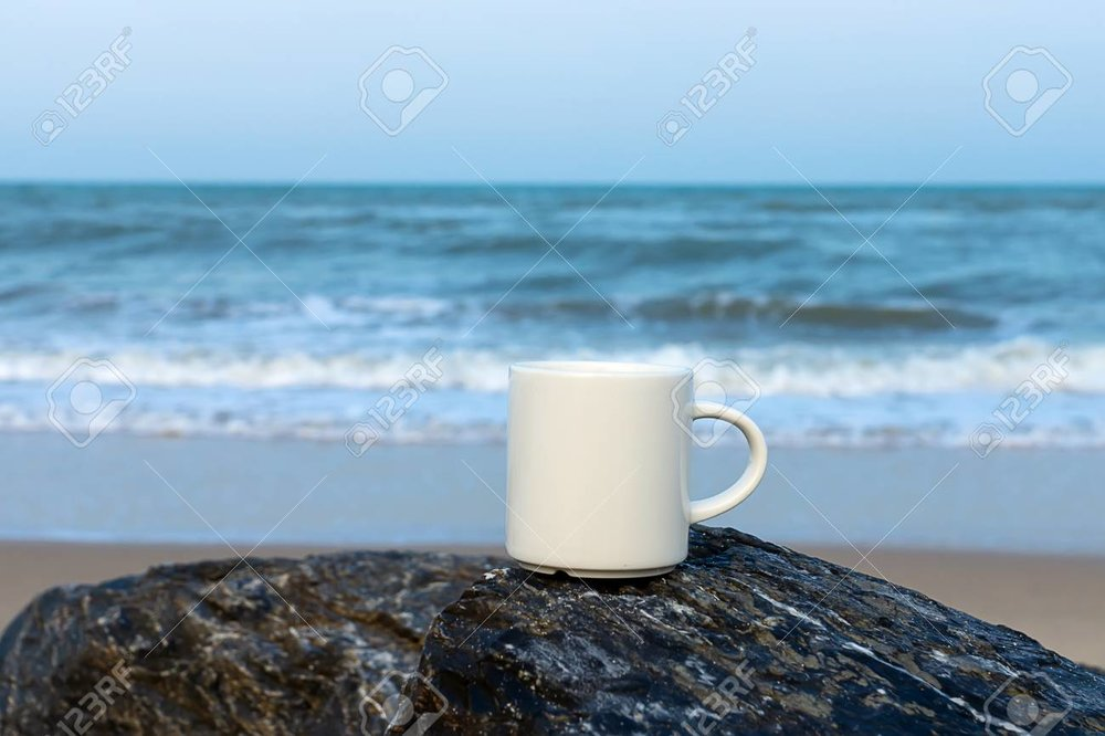 99871223-white-coffee-cup-on-the-rock-at-sea-.jpg