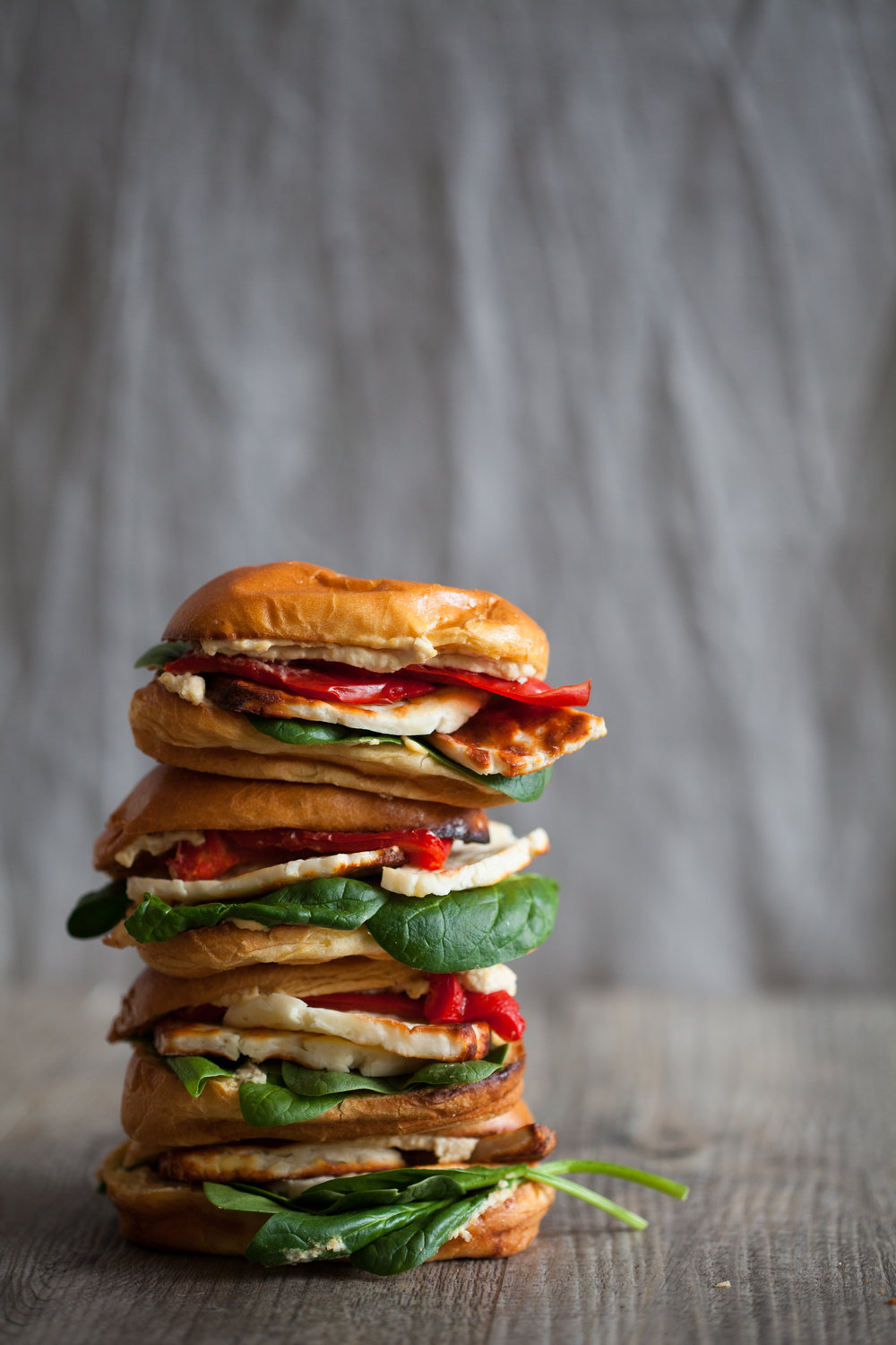 Solo Element. Placing to the left and keeping the background and surface neutral makes the stack really pop, particularly the reds and greens. The two stalks spilling out of the bottom bun, give balance and weigh down the image. This is classic rule of thirds.