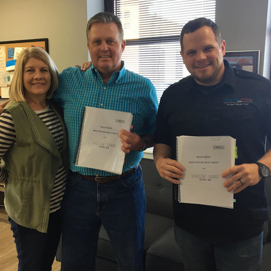 Our Cumming, GA franchisees, the Mitchell family (left) stand with Shuckin' Shack Franchising CEO, Jonathan Weathington (right) after being awarded their franchise - April 2018.