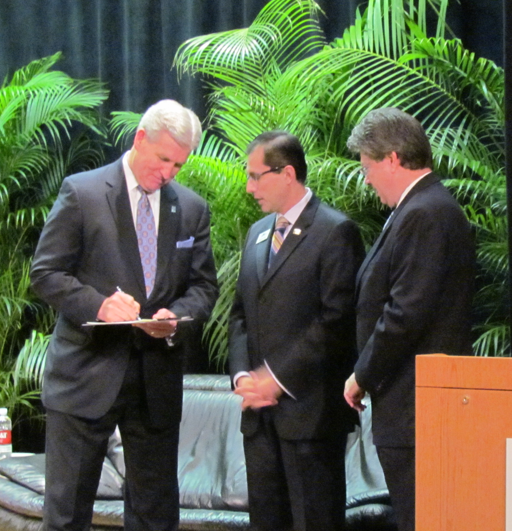 Northwood President Keith A. Pretty, JD signs the partnership agreement as Alfredo Ortiz and Dr. Tom Duncan look on.
