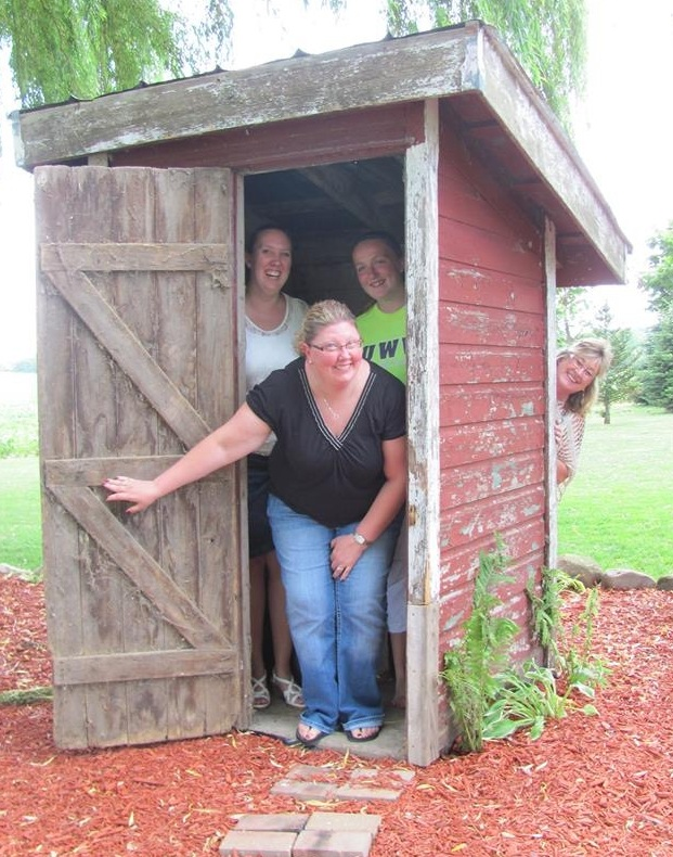 sara being goofy with some friends in an outhouse!