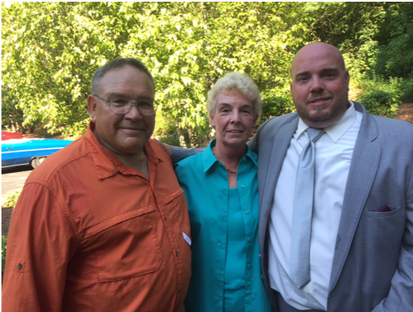 korey and his parents at a friend's wedding