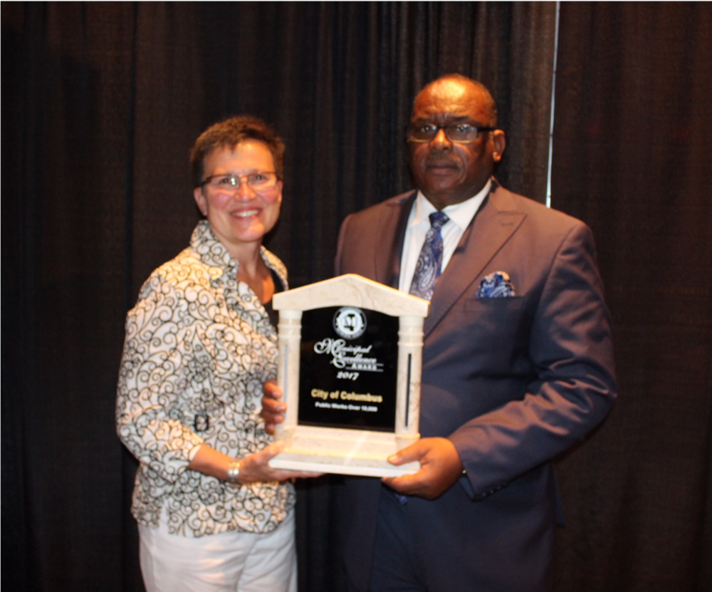 City of Columbus Mayor Robert E. Smith, Sr. (with Multistate Trust Environmental Programs Director Lauri Gorton) accepts the 2017 MML award for the 7th Avenue North ditch improvement project.