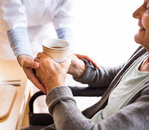 Senior recevant une bonne tasse de thé chaude d'un assistant