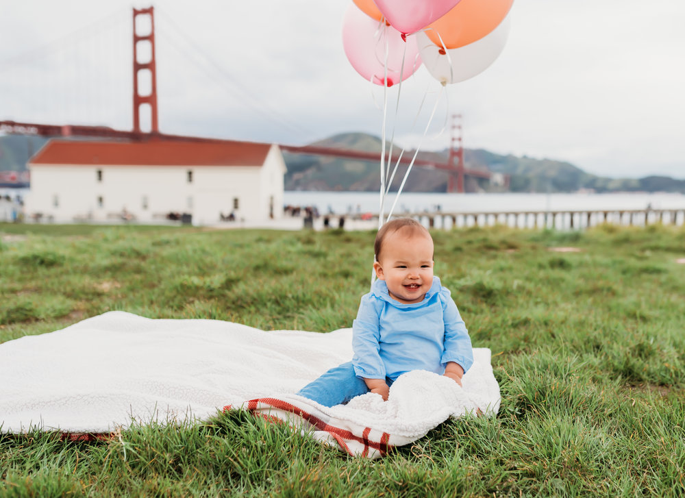 White blanket and pink and white balloons at Crissy Field