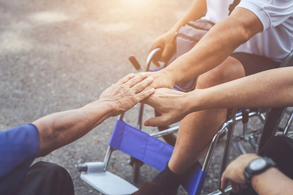Three people in wheelchairs put an arm in the centre to pile their three hands in a gesture of solidarity.