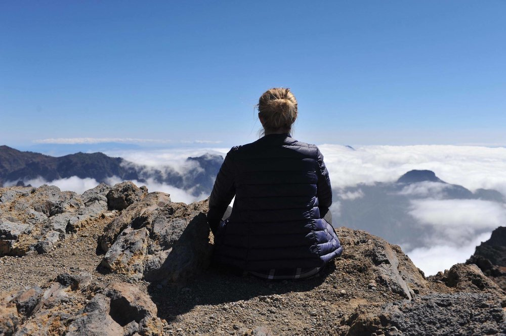 Daria Rasmussen sitting and meditating on the top of a mountain above the clouds.jpg