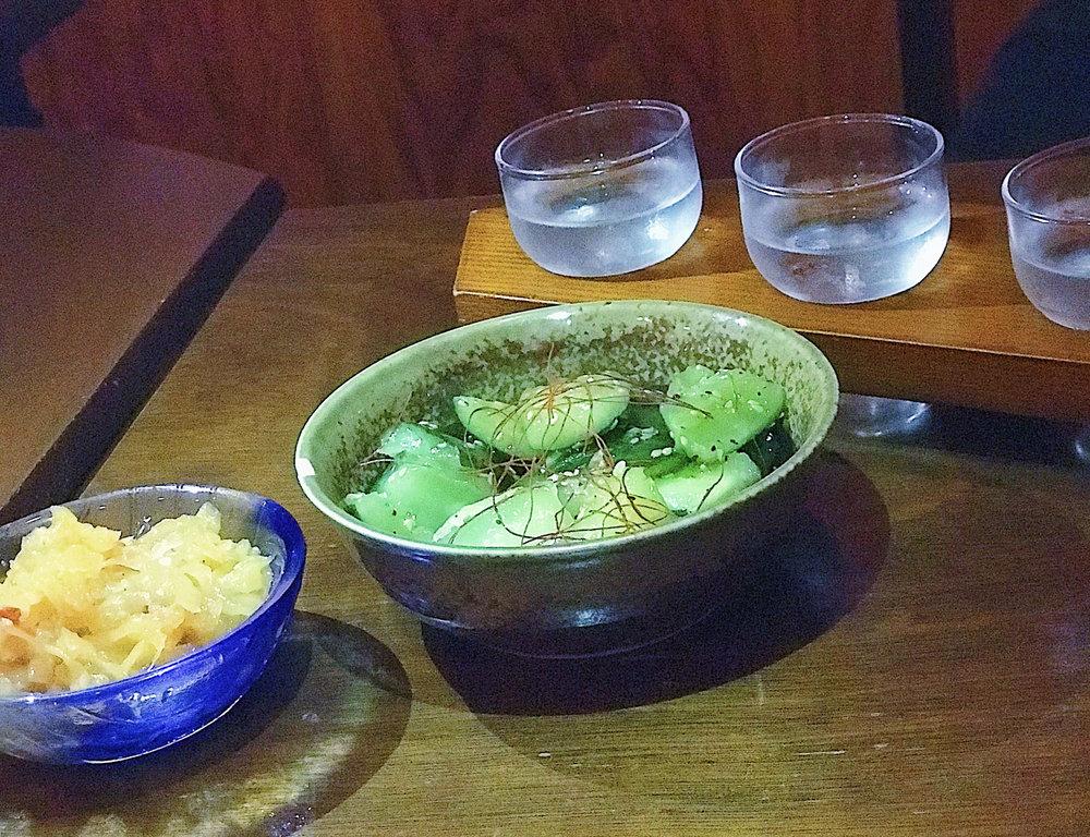 Starters. From left to right: seasoned jellyfish, cucumber pickles, sake flight.