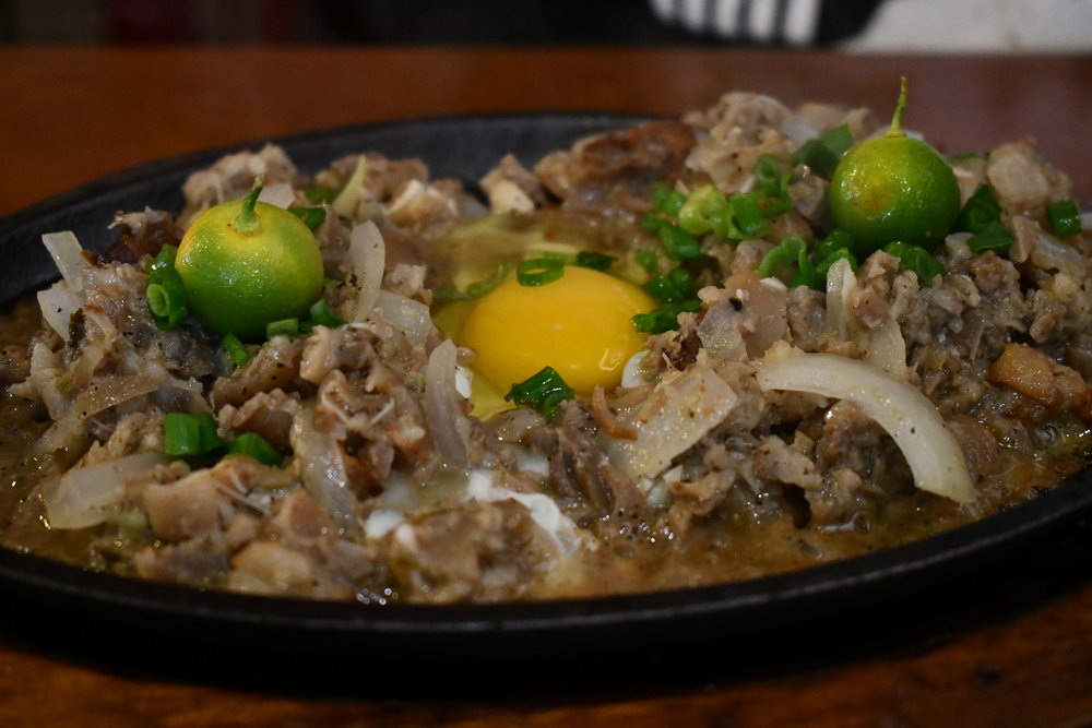 Sisig . A Filipino hash. Chopped bits of pork that have been boiled, grilled, and fried along with various vegetables. Served with a raw egg on a sizzling cast iron platter.