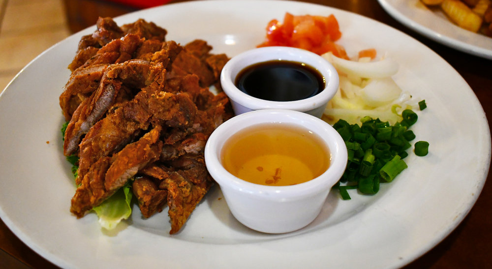 Fried Pork.  Crispy deep-fried pork shoulder served with tomatoes and onions, spiced vinegar, and soy sauce.